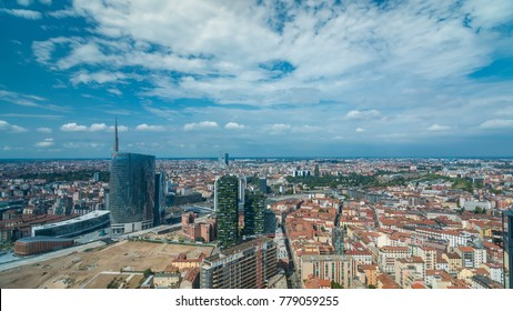 Milan aerial view of modern towers and skyscrapers and the Garibaldi railway station in the business district timelapse fiew from rooftop. Houses with red roofs. Blue cloudy sky at summer day