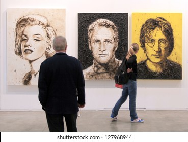 MILAN - APRIL 08: A man and a girl look at paintings representing Marylin Monroe, Paul Newman and John Lennon at MiArt, international exhibition of modern art on April 08, 2011 in Milan, Italy