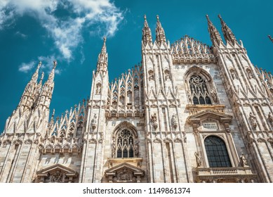 Milan Cathedral (Duomo di Milano), Italy. It is a main landmark of Milan. Luxury facade of Milan Cathedral close-up. Gothic decorations on the blue sky background. Famous ornate architecture of Milan.