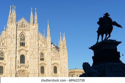 Milan duomo or cathedral against bright blue summer sky with silhouette of king Victor Emanuel covered in doves
