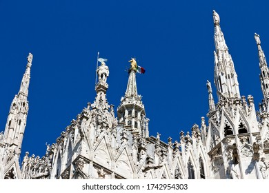Milan Duomo Cathedral, gothic spires and golden statue of Madonna with italian flag. Blue sky background, top landmark of historic Milan city.