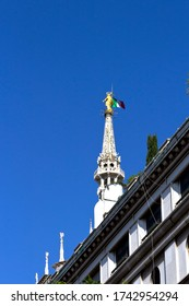 Milan Duomo Cathedral, view on golden statue of Madonna with italian flag placed on the highest gothic spire. Blue sky background, top landmark of historic Milan city.