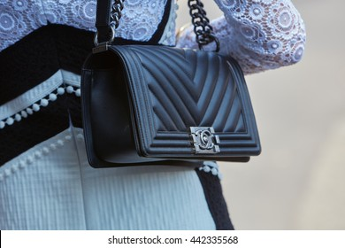 MILAN - FEBRUARY 18: Woman poses for photographers with black Chanel leather bag before Canali fashion show, Milan Men's Fashion Week street style on June 18, 2016 in Milan.