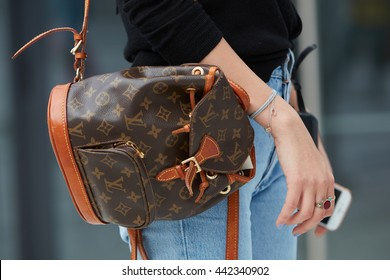 MILAN - FEBRUARY 18: Woman poses for photographers with Louis Vuitton small backpack before Canali fashion show, Milan Men's Fashion Week street style on June 18, 2016 in Milan.