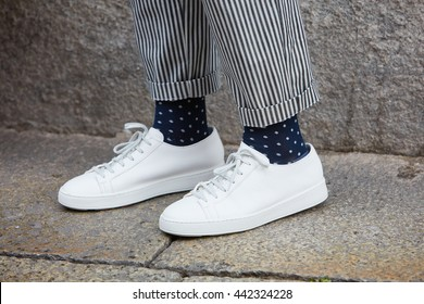 MILAN - FEBRUARY 19: Man poses for photographers with white sneakers shoes before Missoni fashion show, Milan Men's Fashion Week street style on June 19, 2016 in Milan.