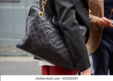 MILAN - FEBRUARY 19: Woman poses for photographers with Chanel leather bag before Boglioli fashion show, Milan Men's Fashion Week street style on June 19, 2016 in Milan.