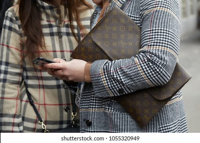 MILAN - FEBRUARY 21: Man with Louis Vuitton bag looking at smartphone before fashion Albino Teodoro show, Milan Fashion Week street style on February 21, 2018 in Milan.