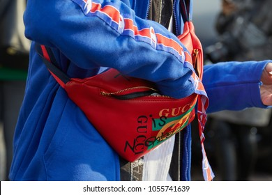 MILAN - FEBRUARY 21: Man with red Gucci pouch and blue jacket before Gucci fashion show, Milan Fashion Week street style on February 21, 2018 in Milan.
