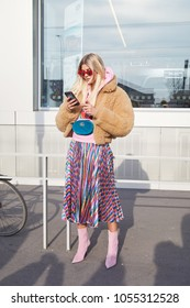 MILAN - FEBRUARY 21: Woman with beige fur coat, blue velvet Gucci pouch and striped metallic skirt before Gucci fashion show, Milan Fashion Week street style on February 21, 2018 in Milan.