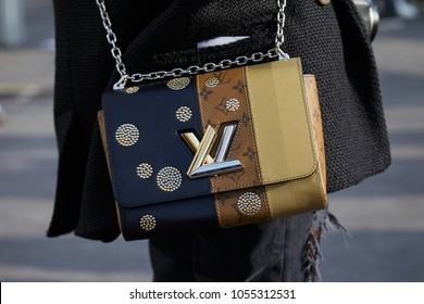 MILAN - FEBRUARY 21: Woman with beige, brown and blue Louis Vuitton bag with golden and silver logo before Gucci fashion show, Milan Fashion Week street style on February 21, 2018 in Milan.