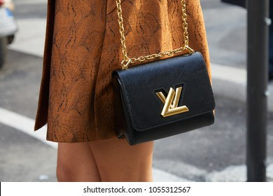 MILAN - FEBRUARY 21: Woman with black Louis Vuitton bag with golden logo and brown jacket before Gucci fashion show, Milan Fashion Week street style on February 21, 2018 in Milan.