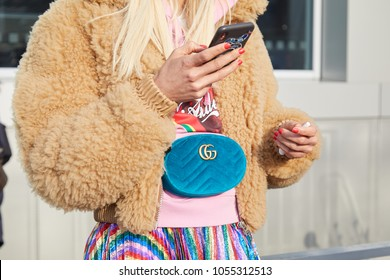 MILAN - FEBRUARY 21: Woman with blue velvet Gucci pouch and beige fur jacket looking at smartphone before Gucci fashion show, Milan Fashion Week street style on February 21, 2018 in Milan.