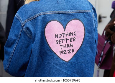 MILAN - FEBRUARY 21: Woman with blue jeans jacket with pink heart with 'Nothing better than pizza' motto before fashion Albino Teodoro show, Milan Fashion Week street style on February 21, 2018
