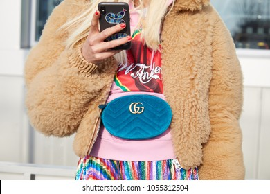 MILAN - FEBRUARY 21: Woman with brown fur jacket blue velvet Gucci pouch looking at smartphone before Gucci fashion show, Milan Fashion Week street style on February 21, 2018 in Milan.