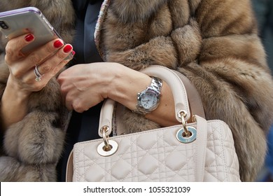 MILAN - FEBRUARY 21: Woman with Chopard watch and Christian Dior bag looking at smartphone before fashion Albino Teodoro show, Milan Fashion Week street style on February 21, 2018 in Milan.
