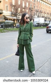 MILAN - FEBRUARY 21: Woman with green jacket and trousers before Alberta Ferretti fashion show, Milan Fashion Week street style on February 21, 2018 in Milan.