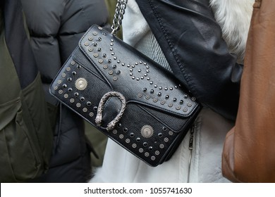 MILAN - FEBRUARY 21: Woman with Gucci black leather bag with studs decoration before Gucci fashion show, Milan Fashion Week street style on February 21, 2018 in Milan.