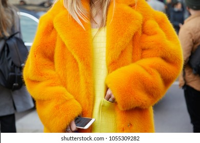 MILAN - FEBRUARY 21: Woman with orange fur coat and yellow dress before Alberta Ferretti fashion show, Milan Fashion Week street style on February 21, 2018 in Milan.