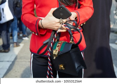 MILAN - FEBRUARY 21: Woman with red jacket and black leather Gucci bag before Gucci fashion show, Milan Fashion Week street style on February 21, 2018 in Milan.
