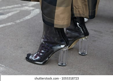 MILAN - FEBRUARY 21: Woman with transparent high heel shoes and brown and black trousers before fashion Albino Teodoro show, Milan Fashion Week street style on February 21, 2018 in Milan.