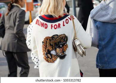 MILAN - FEBRUARY 21: Woman with white sweater with tiger design and red 'blind for love' writing before Gucci fashion show, Milan Fashion Week street style on February 21, 2018 in Milan.