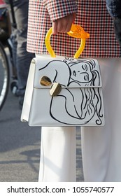 MILAN - FEBRUARY 21: Woman with white leather bag with woman design and orange handle before Gucci fashion show, Milan Fashion Week street style on February 21, 2018 in Milan.