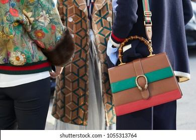 MILAN - FEBRUARY 21: Women with Gucci leather bag in brown, green and red leather and floral jacket before Gucci fashion show, Milan Fashion Week street style on February 21, 2018 in Milan.