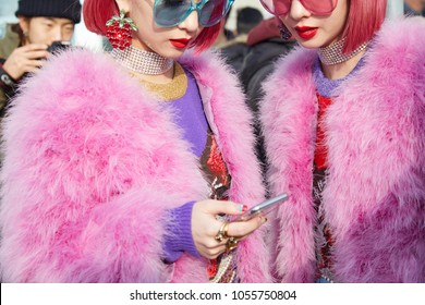 MILAN - FEBRUARY 21: Women with pink fur coat and hair looking at smartphone before Gucci fashion show, Milan Fashion Week street style on February 21, 2018 in Milan.