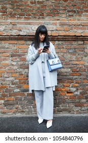 MILAN - FEBRUARY 22: Laura Comolli looking at smartphone before Max Mara fashion show, Milan Fashion Week street style on February 22, 2018 in Milan.