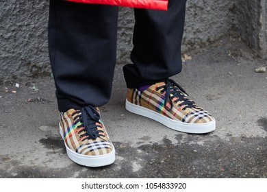 MILAN - FEBRUARY 22: Man with brown checkered shoes with rainbow before Fendi fashion show, Milan Fashion Week street style on February 22, 2018 in Milan.