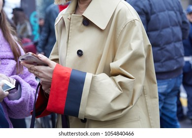 MILAN - FEBRUARY 22: Woman with beige trench coat with red and blue cuffs holding smartphone before Max Mara fashion show, Milan Fashion Week street style on February 22, 2018 in Milan.