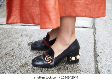 MILAN - FEBRUARY 22: Woman with black leather Gucci shoes and orange skirt before Max Mara fashion show, Milan Fashion Week street style on February 22, 2018 in Milan.