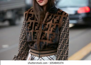MILAN - FEBRUARY 22: Woman with brown fur jacket with Fendi logo in black before Fendi fashion show, Milan Fashion Week street style on February 22, 2018 in Milan.