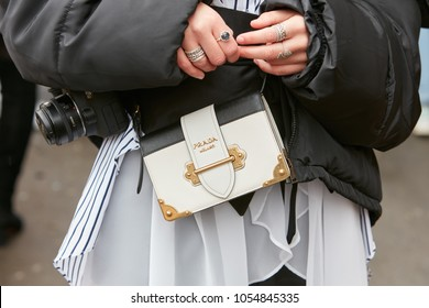 MILAN - FEBRUARY 22: Woman with Prada black and white leather bag and rings before Fendi fashion show, Milan Fashion Week street style on February 22, 2018 in Milan.