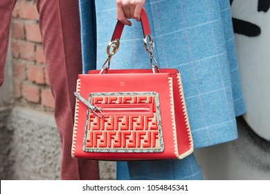 MILAN - FEBRUARY 22: Woman with red Fendi leather bag with logo decoration and blue coat before Fendi fashion show, Milan Fashion Week street style on February 22, 2018 in Milan.