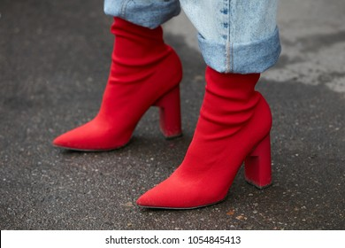 MILAN - FEBRUARY 22: Woman with red pointed high heel shoes and blue jeans trousers before Fendi fashion show, Milan Fashion Week street style on February 22, 2018 in Milan.