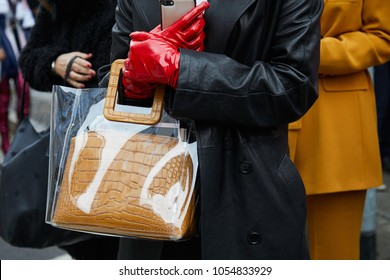 MILAN - FEBRUARY 22: Woman with transparent bag with beige crocodile leather bag inside and red gloves before Max Mara fashion show, Milan Fashion Week street style on February 22, 2018 in Milan.