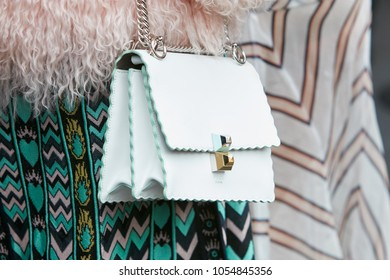 MILAN - FEBRUARY 22: Woman with white and pastel green Fendi bag and green decorated skirt before Fendi fashion show, Milan Fashion Week street style on February 22, 2018 in Milan.