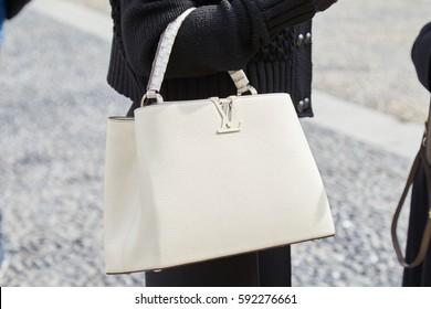 MILAN - FEBRUARY 22: Woman with white leather Louis Vuitton bag before Cristiano Burani fashion show, Milan Fashion Week street style on February 22, 2017 in Milan.