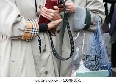 MILAN - FEBRUARY 22: Women with gray trench coat and Celine transparent bag before Fendi fashion show, Milan Fashion Week street style on February 22, 2018 in Milan.