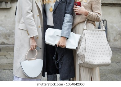 MILAN - FEBRUARY 22: Women with light color bags before Max Mara fashion show, Milan Fashion Week street style on February 22, 2018 in Milan.