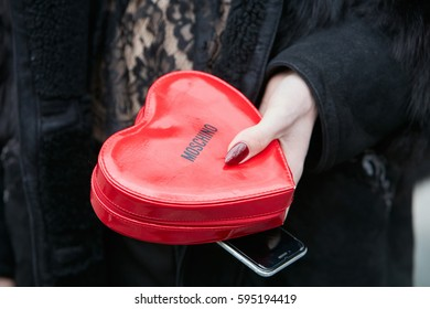 a303f7bdec35 MILAN - FEBRUARY 24  Man with heart shaped red Moschino bag and black coat  before
