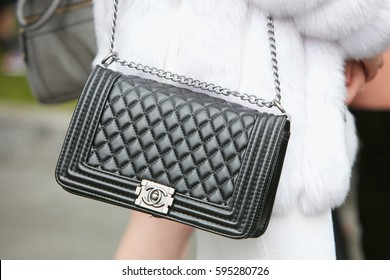 MILAN - FEBRUARY 24: Woman with black Chanel leather bag and white fur before Emporio Armani fashion show, Milan Fashion Week street style on February 24, 2017 in Milan.