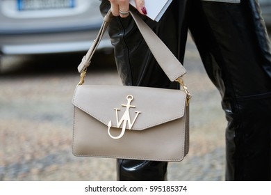 MILAN - FEBRUARY 24: Woman with JW Anderson beige leather bag and golden symbol before Tod's fashion show, Milan Fashion Week street style on February 24, 2017 in Milan.