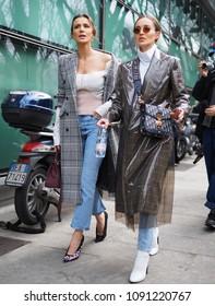 MILAN - FEBRUARY 25, 2018: Two fashionable women posing for photographers in the street before ARMANI fashion show, during Milan Fashion Week Woman fall/winter