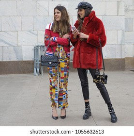 MILAN - FEBRUARY 25, 2018:Two fashionable women posing for photograpers in Duomo square after STELLA JEAN fashion show, during Milan Fashion Week Woman fall/winter 2018/19 in Milan, Italy.