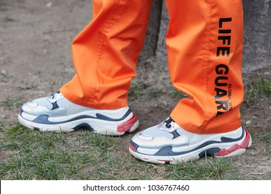 MILAN - FEBRUARY 25: Man with Balenciaga sneakers and orange Life Guard trousers before Emporio Armani fashion show, Milan Fashion Week street style on February 25, 2018 in Milan.