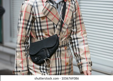 MILAN - FEBRUARY 25: Man with beige Burberry raincoat and black Dior bag before Emporio Armani fashion show, Milan Fashion Week street style on February 25, 2018 in Milan.