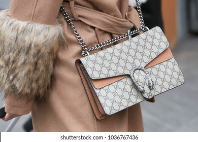 MILAN - FEBRUARY 25: Woman with Gucci bag with beige coat with fur details before Emporio Armani fashion show, Milan Fashion Week street style on February 25, 2018 in Milan.