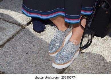 MILAN - FEBRUARY 25: Woman poses for photographers with silver glitter shoes before Genny show Milan Fashion Week Day 1, Fall/Winter 2015/2016 street style day 1, on February 25, 2015 in Milan.